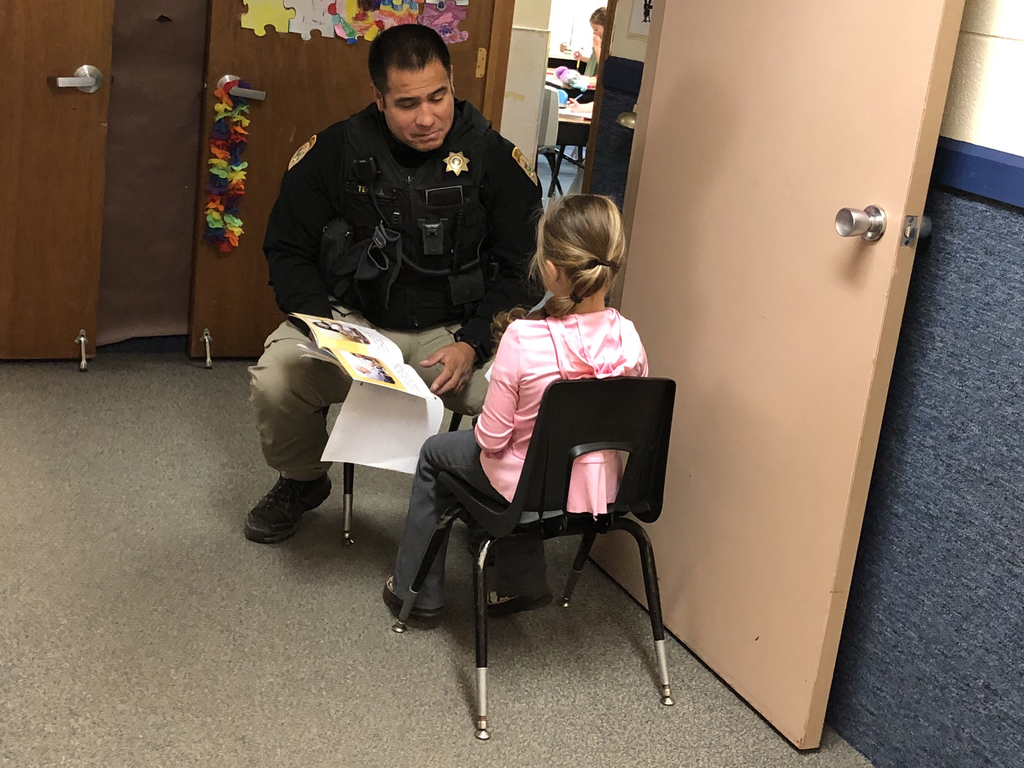 Deputy Terrill reading with a student.