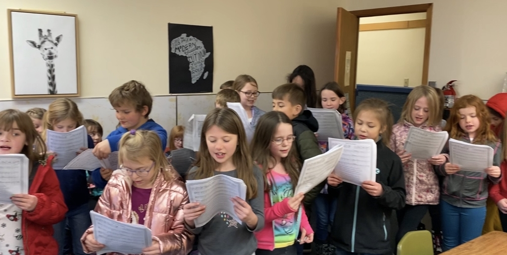 Students in the after school choir singing carols to teachers in their rooms.