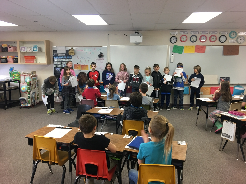 Third grade students lined up facing second grade, performing reader's theater