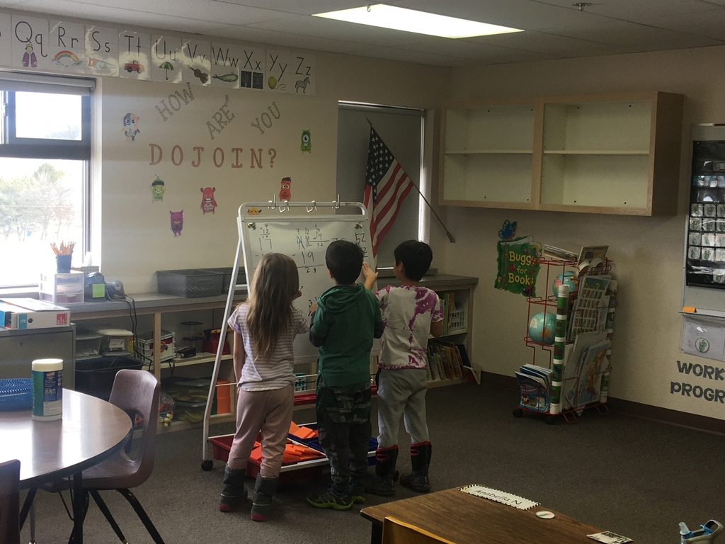 Three second graders work at a whiteboard easel on subtraction.